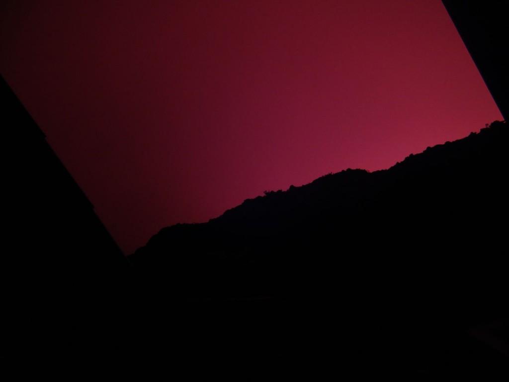 Rot erleuchteter Himmel über den Hütten am Kraterrand