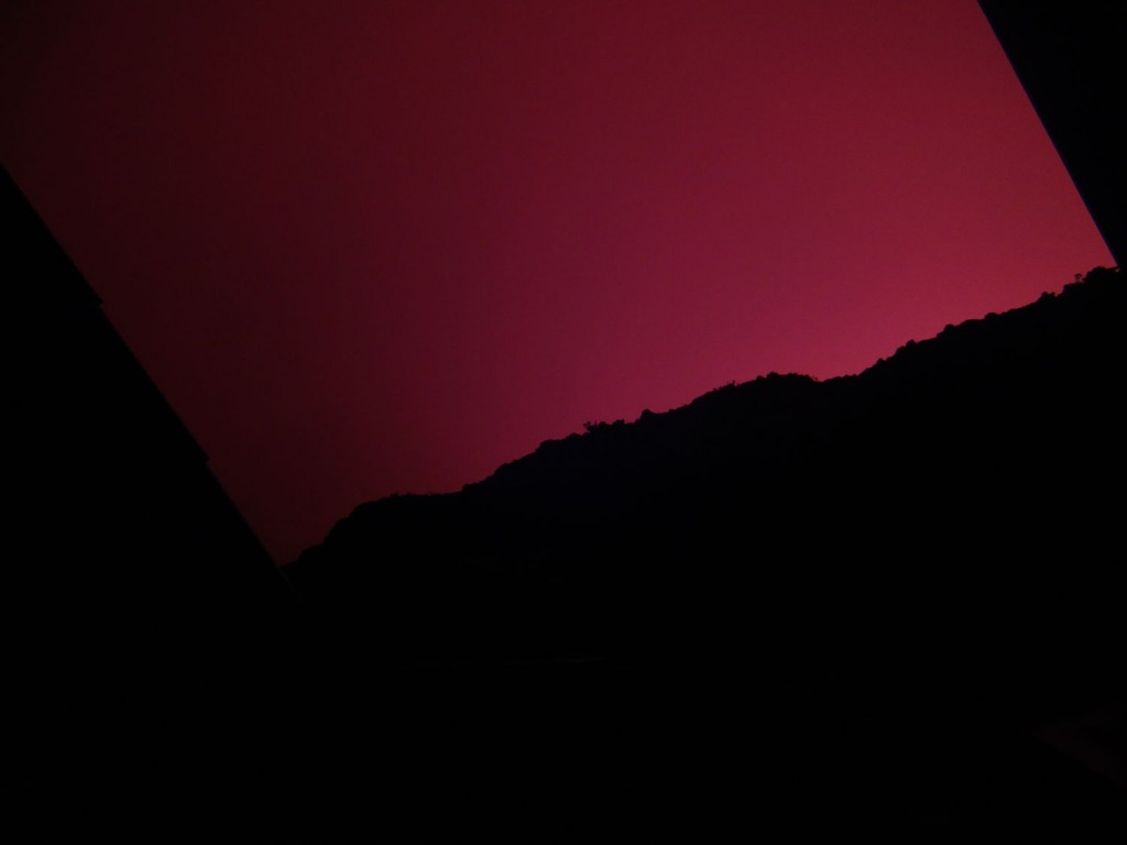 Red glowing night over the huts on the rim of the crater