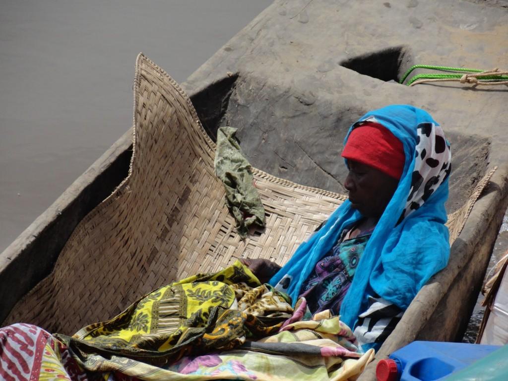 Frau in der Piroge längs zum Schiff